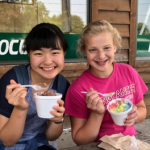 Two young girls eating ice cream